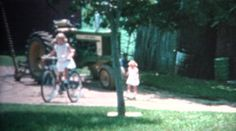 (8mm Vintage) 1962 Girl Riding Bike Around the Family Farm. Iowa, USA. http://www.pond5.com/stock-footage/51447050?ref=StockFilm keywords:girl, riding, bike, yard, grass, offroad, cute, tractor, farmland, farmer, agriculture, 1962, rural, living, 1960s, farm, iowa, 8mm, footage, film, home video, home movie, homemade, retro, vintage, classic, old, reel to reel, 16mm, projector, super 8, amateur, grainy, archive, nostalgia, memories, restore, preserve, romance, cinematography, golden age…