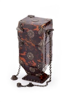 "Selkirk Auctioneers & Appraisers | Full Details for Lot 11 TORTOISE SHELL FIREPLACE ACCESSORY BOX.  Continental, late 18th to early 19th century. Two-part tower form with fitted lid and all-over silver mounts, handles separate on chairs, the whole raised on pedestal support. 8.3""h.  Estimate $ 300-500"