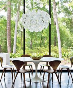 In this breakfast area, iconic pieces of 20th-century design—a Saarinen table and walnut Cherner chairs, all from Design Within Reach—overlook a peaceful bayou view, captured by windows in dark bronze anodized frames.