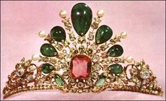 Emerald and Diamond Tiara - Iranian National Royal Jewels: Its basic design is of a sunburst, with a 25 ct. pink spinel in the center. Each ray ends in a diamond blossom with a single pearl or emerald. The emeralds have holes in them which are covered with small diamonds. The holes suggest that the emeralds were previously used in other pieces. The largest emerald is 20 cts.