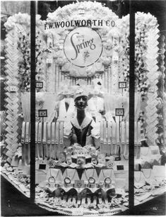 """Woolworth Spring Display - All the display windows seem to have been photographed at night and illuminated by lights in the display window. F. W. Woolworth Co. was a competitor of Sterling. This window displays """"White for Spring"""" women's accessories. They include belts, buckles, buttons, and bracelets and some fabric things I can't identify. Prices are 5¢ to 20¢. The manikin head wears a little white cap and has a white collar. The image is numbered"""