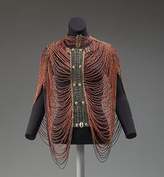 Bodice, 20th century. Worn by the Dinka peoples in Africa. Made of fiber, glass beads, and cowrie shell.