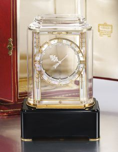 Rock crystal, mother-of-pearl, onyx and diamond 'Model A' Mystery Clock, Cartier, 1927 The millegrain-set diamond hands set within a gold frame and a chapter ring applied with mother-of-pearl, rose diamonds and raised gold Roman numerals, the bevelled rock crystal case on a onyx rectangular base, measuring approximately 141 x 90 x 52mm, unsigned, numbered, French assay mark, fitted case and charge key.