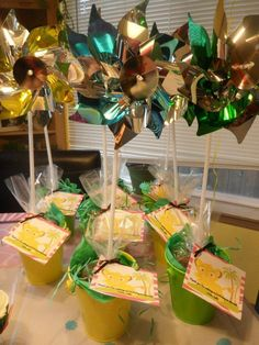 """""""Flower pot"""" party favors (Lion King birthday party for my 2 yr old)- Tins are from the Target one spot. Inside is tissue paper and Easter grass to add bulk. Bags have chocolate covered raisins and m&m's for """"dirt"""", and gummy worms for """"grub"""". Pinwheels for """"flowers"""", from Walmart."""