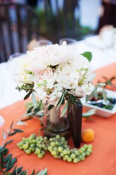 Grapes, roses and terra cotta table runners lend a Tuscan feel to the al fresco reception. Janae Shields Photography.