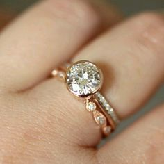 2 carat conflict-free rose gold engagement ring (seen with two thin decorative bands to either side)