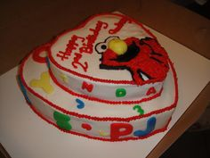 Elmo cake! Heart shaped cakes with fondant letters and a hand piped Elmo! Made by Tastes So Sweet.