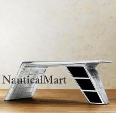 NauticalBase Aluminium Aviator Wing Desk Handmade Furniture *BEAUTIFUL AND DECORATIVE TABLE *MADE OF WOOD AND ALUMINIUM *EASILY ADJUSTABLE ANY PLACE *EXCELLENT QUALITY OF RAW MATERIAL & CAN BE USED HOME AND OFFICE DECOR *SIZE: 78W x 41D x 30H *ALUMINIUM HAS A MATTE FINISH THATS LIGHTLY DISTRESSED FOR A VINTAGE LOOK; INTENTIONAL NICKS, DINGS, SMALL SCRATCHES & OTHER IMPERFECTIONS ARE TO BE EXPECTED AND ADD TO THE CHARACTER AND UNIQUENESS OF EACH ITEM Inspired by streamlined World War...