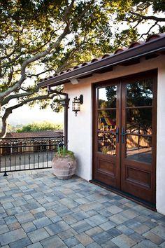 Clay tile roof, dark brown gutters, wrought iron fixtures (lights, door handles), stucco and wood doors