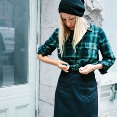 noticed: knotting the button-down shirt. ella is wearing a madewell green flannel boyshirt in barlow plaid, black high-waisted sailor skirt, and a black simple ribbed beanie hat.
