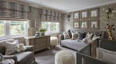 Gray boy's nursery features walls clad in taupe and gray ark themed wallpaper, Andrew Martin Ark Wallpaper in Parchment, lined with a collection of baby animal photographs by Sharon Montrose over a gray velvet daybed lined with white and gray pillows.
