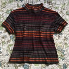"Vintage 90s grunge striped sweater shirt Vintage 90s grunge orange, red, teal, burgundy and brown striped mock neck sweater shirt. Short sleeved knit sweater shirt. Has a mock neck. Has good stretch. Measurements are taken laying flat: armpit to armpit: 19.5"" length: 20"" Vintage Tops"