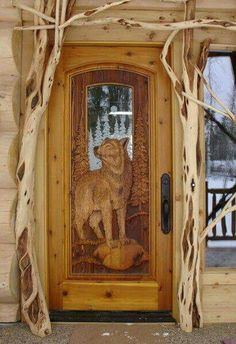 "Amazing wood carved door! I also love the branches ""framing"" the door. The glass with etched evergreen trees and the wolf standing strong and proud is just beautiful."