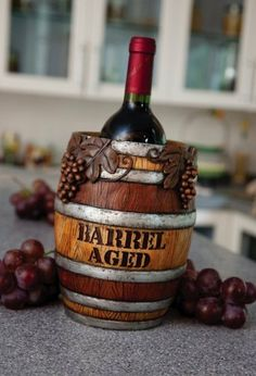 "Wine Barrel Bottle Holder by Evergreen Enterprises, Inc. $16.99. Made of hand-painted resin. 6""H x 6""W x 8""L. Perfectly holds a bottle of wine. Fun and unexpected, this is a bottle holder that makes a witty statement on your countertop. A wine bottle fits perfectly into this resin barrel, marked ""Barrel Aged"" with an implied wink. Presentation adds to the flair of the evening, and the Wine Barrel Bottle Holder is one that guests will remember.. Save 37%!"