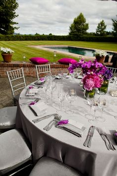 beautiful table decor - grey tablecloths with grey napkins (linens) with programs folded horizontally into napkins and fuschia and purple flower centerpieces - no charger plates or plate settings