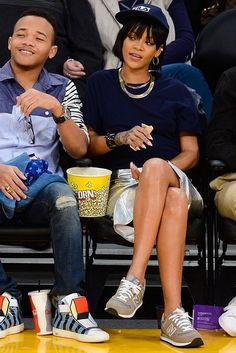 Rihanna wearing Fallon Wide Herringbone Necklace, Jonathan Simkhai Metallic Leather Pencil Skirt, New Balance 574 Light Grey and Silver Sneakers and Topshop Blue Roll Back Crop Tee.