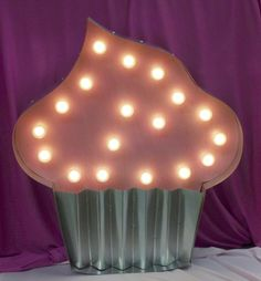 Hollywood Marquee Cupcake with Pink Sprinkled Frosting, and metal wrapper.