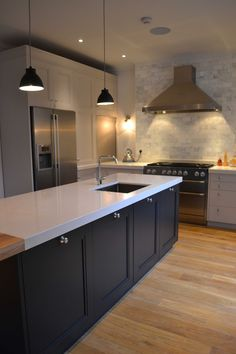 The quartz composite work surface is used for serving food and clearing away while the family use the oak breakfast bar themselves for eating breakfast and lunch.   www.woodstockfurniture.co.uk