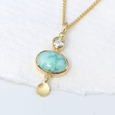 Lilia Nash Jewellery Turquoise and Diamond Pendant in 18ct Gold; This dainty turquoise and diamond pendant is completely handmade in solid recycled 18ct yellow gold. A beautiful light blue turquoise with blue-green webbing is the star of the pendant. It is from the Carico Lake mine in the USA. The turquoise measures 10mm x 7mm and weighs 2.03 carats. This stone is 100% natural and is not treated. The turquoise rough was purchased from the current mine owner and then expertly cut by a…