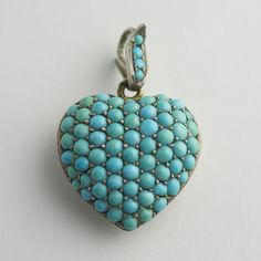 "Victorian Pavé Puffy Turquoise Heart Locket. ""A pavé of turquoise cabochons decorates the front of the locket (including the original bale) in perfect symmetry. The back features an aperture for a photo or a lock of hair ... The heart measures 1"" across at its widest point and 15/16"" long."" circa 1880"