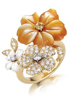 An 18k yellow gold ring set with white and yellow mother-of-pearl flowers adorned with diamonds and sapphire.