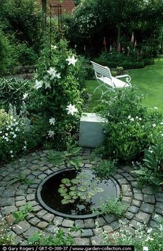 Make water feature at one edge of patio area. Surround all of patio with plants like this one does. Bricks planted with moss? in between.