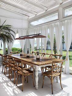 coin repas élégant sur la terrase blanche avec rideaux blancs