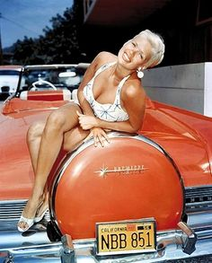 Jane Mansfield posing on the back of a Lincoln Premier, 1957.
