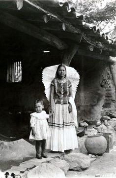 Mujer Tehuana en traje tradicional sostiene la mano de un niño, ubicacion Tehuantepec México, Fotógrafo A.W. Cutler. Fecha desconocida (posiblemente decada de 1920).