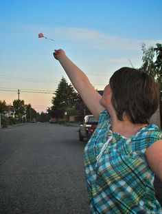 A girl flies her kite on a street in West Seattle
