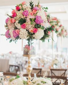 Few things transform a table design quite like a dramatic #centrepiece bursting with #peonies, #roses, and #hydrangea. We're especially fond of how this transparent base showcases a collection of #rosebuds! | Photography By: Elizabeth in Love. | WedLuxe Magazine | #luxury #wedding #luxurywedding #weddinginspiration  #pink #floral #floralarrangement #decor #flowers
