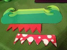 Cut out Elf Shoes from green & patterned paper.  Two pieces per shoe.  Template can be found here: http://www.schoolgirlsamplers.com/pdftutorialspatterns/ElfShoesTemplate.pdf