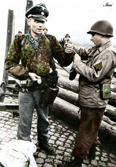 An Untersturmführer (2nd Lieutenant) of the Waffen-SS is searched by an american soldier straight after being captured. The G.I. is just taking the officers' watch.