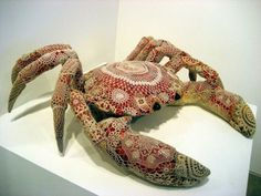 A Vasconcelos hand-crochet covered crab.  The artist considers her crochet to be a drawing or pattern on the work.
