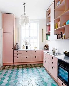 Pink kitchen cabinets and blue tiled floors