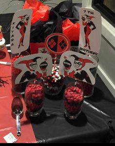 Colored candy in glass jars with printed Harley Quinn I cut and pasted on straw sticks and added sticker letter and numbers for personalization also added tissue paper in the goodie boxes that are shown in another photo of how I made them done by Mamiimely