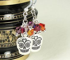 With sugar skull charms and warm colors of marigold, orange, ruby and amethyst, these earrings celebrate Día de los Muertos - the Day of the