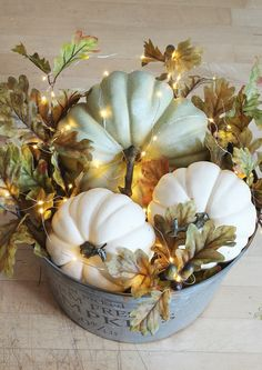 DIY pumpkin craft with three neutral colored pumpkins in a metal bucket. pumpkins are wrapped in fall foliage and christmas lights
