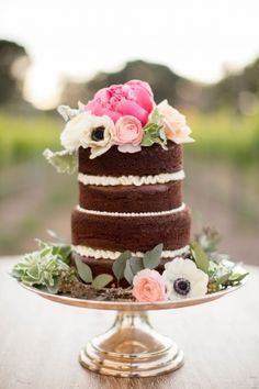 small chocolate naked cake on a silver stand with pink flowers