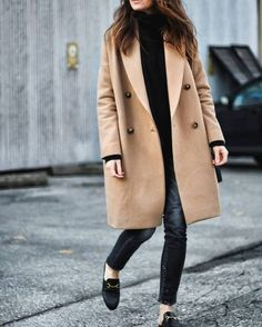 Cedar Atkins is wearing black loafers with black skinny jeans and a striking double breasted camel coat, creating a sleek street style we love. Top: The Kooples, Coat: Sosken Studios, Jeans: R13 Denim, Loafers: Gucci.