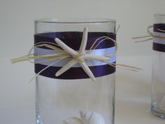Set of 12 beach inspired glass vase centerpieces accented with starfish, shells and customized ribbon for weddings. $148.00, via Etsy.