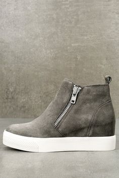 """Kick your street style OOTD up a notch with the Steve Madden Wedgie Grey Suede Leather Hidden Wedge Sneakers! These sleek genuine suede sneakers have a rounded toe, stylish high-top design, and dual, silver side zippers. A hidden wedge heel gives a flattering, mile high leggy look. 1"""" white rubber bumper sole."""