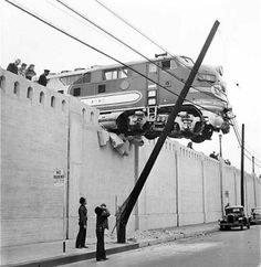 Santa Fe diesel passenger locomotive hangs over Aliso St. after running off the end of its track at Union Station. Jan. 25, 1948.