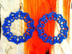 Circle shaped earrings made with tatting technique.