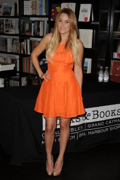 A bright orange flare dress is perf for summer weddings.