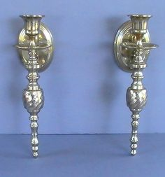 Solid Brass Wall Candle Sconces Swirled Urn Post Set of 2  This set of Grecian Style Sconces are made of a solid brass form, not brass plated and will add warmth and style to your decor for your family to enjoy in your own home. Measures a stately 9.75 inches tall, 2.75 inches wide, and projects 4 inches from wall. Match them up with a great pair of Peg Votive Holders (Sold here separately).  Lacquered With A Heavy Duty, Non-Tarnish Finish.