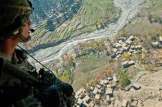 U.S. Army Capt. Scott Hall, aide-de-camp to Brig. Gen. Gary Volesky, 1st Cavalry Division Deputy Commanding General, looks out the door of a UH 60 Black Hawk as it banks hard over a village in the Dawlat Shah district Nov. 15.
