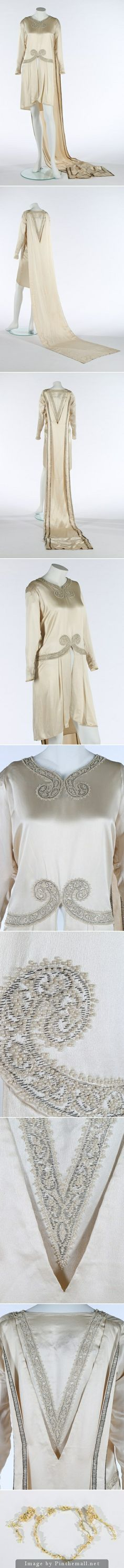 A Callot Soeurs couture ivory satin bridal gown with integral train, 1927. un-labelled, with embroidered curleques to the neck and waist, V to back which is framed by the train which has metal strip embroidered bands to the reverse, front split to skirt which would have revealed the petticoat. KTA