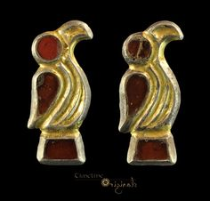 Merovingian Frankish Garnet Bird Brooches ,circa 6th century AD. A pair of cast silver brooches in the form of stylised birds with hooked beaks and scrolled bodies. The eyes, wings and tails are formed by garnets set 'en cloison.' On the reverse, the pin-lugs and catchplates are in place (the pins lost in antiquity). Paired bird brooches are a classic form of garment closure used by the Merovingian Franks and also found in nearby Kent.