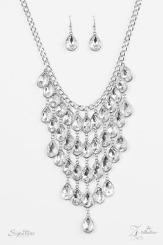 Visit www.DylshJewels.com  The Shanae  Item #Z710 Glittery white gems are pressed into silver teardrop frames, creating a gorgeous tapered fringe below the collar as the sparkling drops link together in vertical rows of blinding shimmer. Features an adjustable clasp closure.  Named after 2017 Rock the Runway winner, Shanae F.  Sold as one individual necklace. Includes one pair of matching earrings.